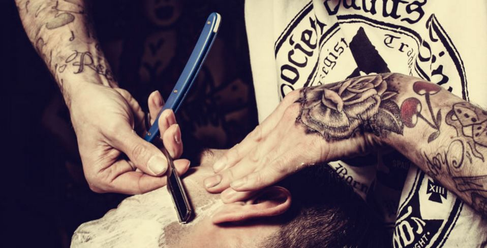 Barber shaving a chin with a straight razor