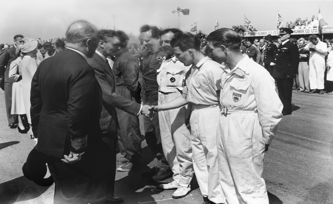 Silverstone, Great Britain. 13th May 1950. King George VI meets the drivers, including a young Stirling Moss, who finished in 2nd position in the 500cc support race, portrait. Photo Credit: Silverstone Classic/LAT Photographic www.latphoto.co.uk