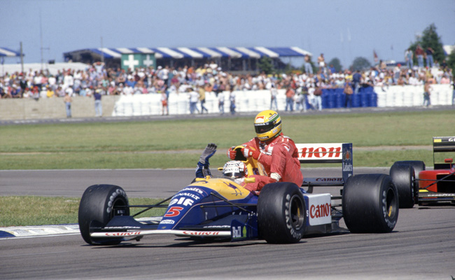 1991 British Grand Prix. Silverstone, Great Britain. 14 July 1991. Nigel Mansell, Williams FW14-Renault, 1st position, gives Ayrton Senna, McLaren MP4/6-Honda, 4th position, a lift back to the pits in one of the most iconic moments in Silverstone's F1 history. World Copyright: LAT Photographic Ref: 35mm transparency 91GBR11