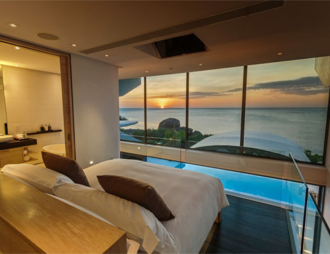 Luxury bedrooms with views of a spectacular sunset at Kata Rocks resort.