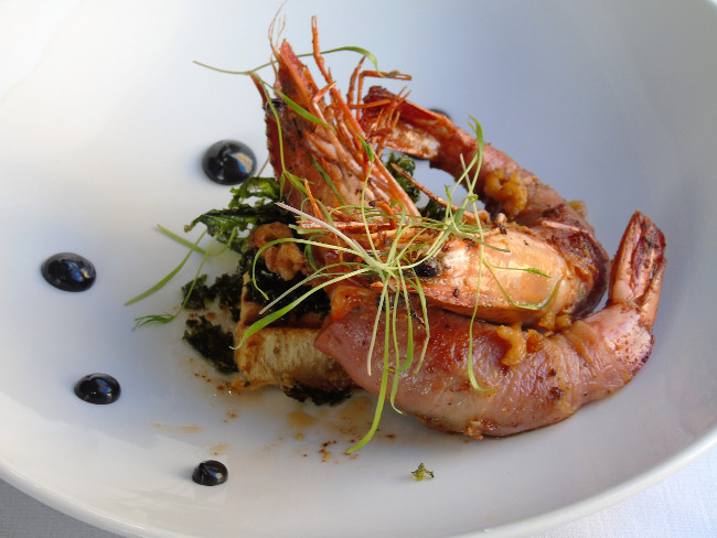 Giant tiger prawns wrapped in sage and Parma ham, chargrilled focaccia bread, black garlic emulsion, crispy curly kale