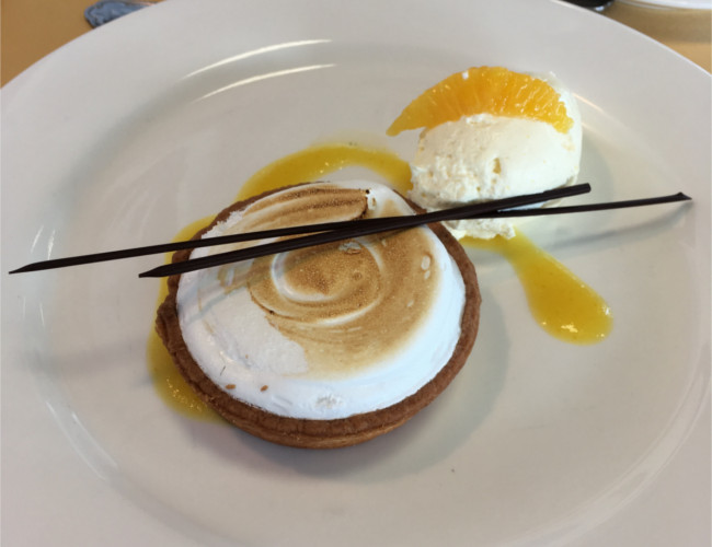 Passion fruit meringue tart with orange cream & chocolate spear.