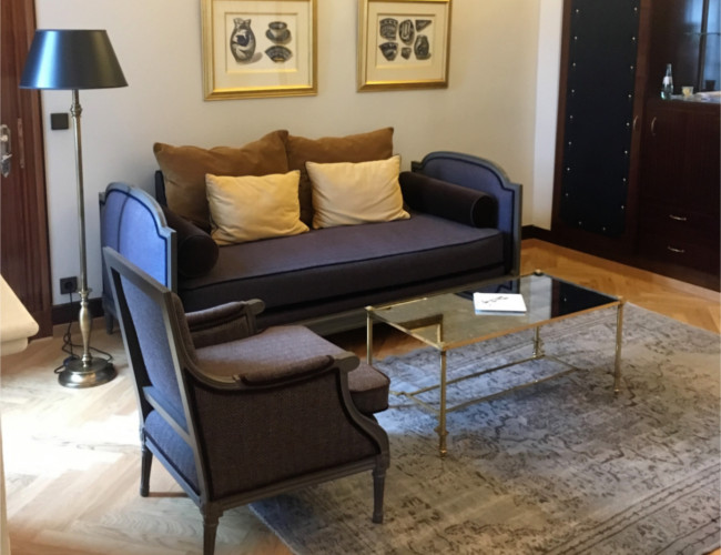 The comfortable chaise lounge style divan, armchair and gold rimmed glass coffee table situated directly opposite the bed.