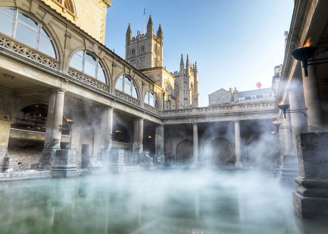 Roman Baths with Bath Abbey in the background, against blue sky, steam rising up