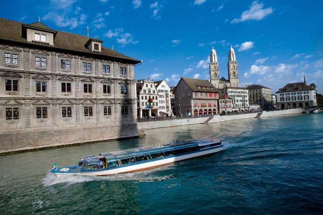 Zurich river cruise on the river Limmat with view towards Town Hall and Grossmuenster.