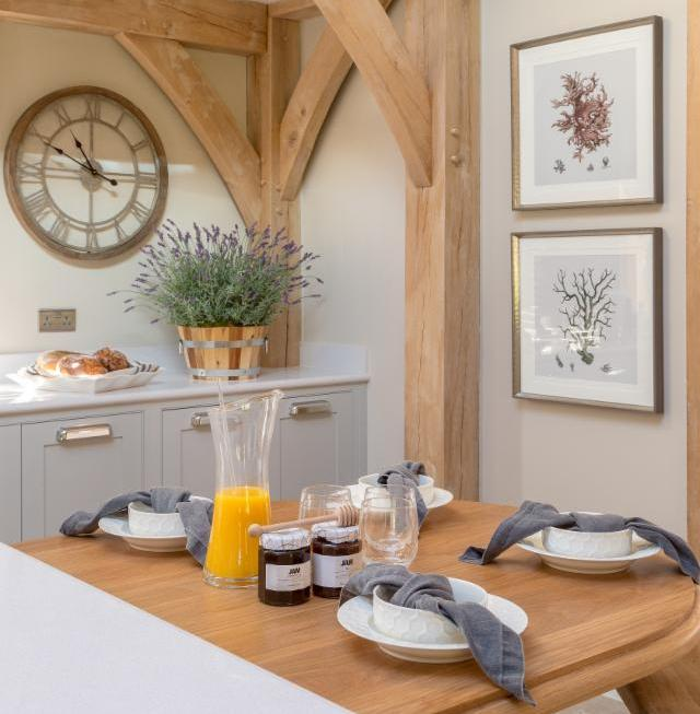 The rustic kitchen diner setting antique style metal framed wall clock and framed prints all add to the country charm in our modern surrey barn project