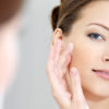 Woman caring of her beautiful skin on the face standing near mirror in the bathroom