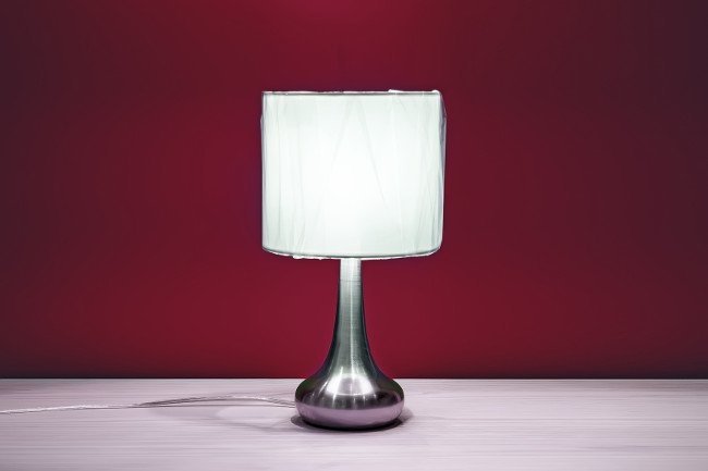 Lamp on a night table next to a bed. Night lamp with round shade standing on a wooden table on a background of red walls to read burns brightly in the dark.