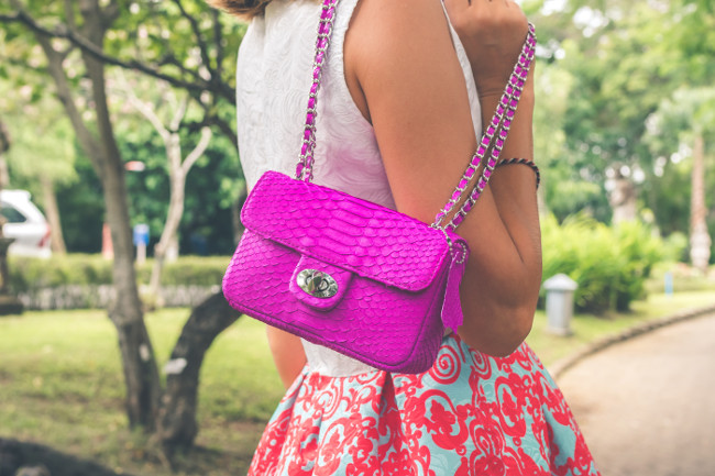 Woman hands with luxury handmade snakeskin leather handbag. Python snake fashionable handbag.