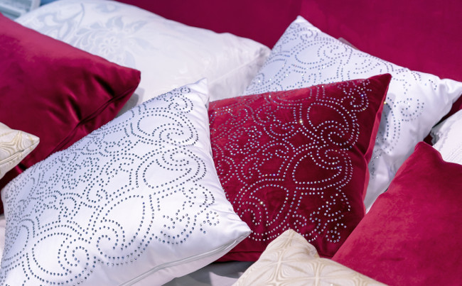 Decorative pillows from velvet and brocade on the bed in the bedroom.