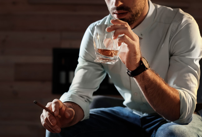 Man with glass of whiskey and cigar at home, closeup. Space for text