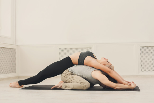 Young couple practicing acroyoga on mat in studio together. Man and woman doing yoga exercise, copy space