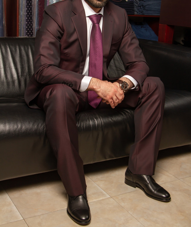 A man in a classic suit is sitting on a black leather sofa, against the background of goods in a clothing store, left-side view. Clothing Italian designers. Wristwatches in brown color