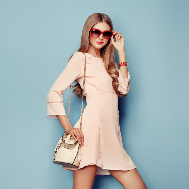 Portrait of Fashion Young woman in Pink Dress. Lady in Stylish Summer Outfit. Girl Posing on a Blue Background. Stylish Hairstyle. Model Posing with Summer Handbag and Sunglasses