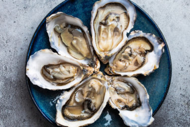 Set of half dozen fresh opened oysters in shell served on rustic blue plate on gray stone background, close up, top view. Oysters concept
