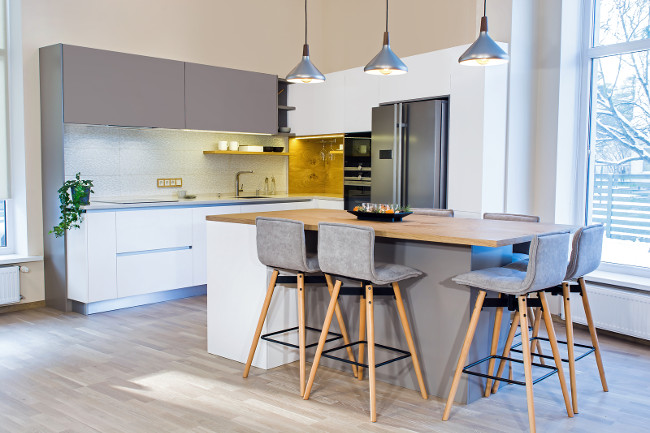 Modern kitchen design in light home interior. Kitchen island in the room. Kitchen and living room. European furniture, design, technologies. Float Pendant Light. Bar stools. Appliances and decorations