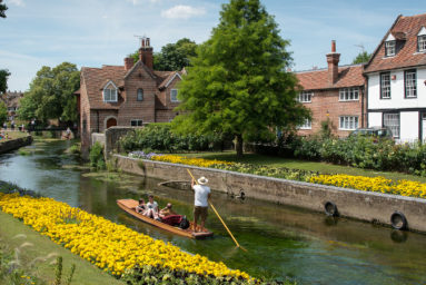 Canterbury Kent United Kingdom - 7 July 2017:Tourist people taking a romantic boat ride in the canal of the river stour at the beautiful Chartham gardens in the center of the city of Canterbury in Kent United Kingdom.
