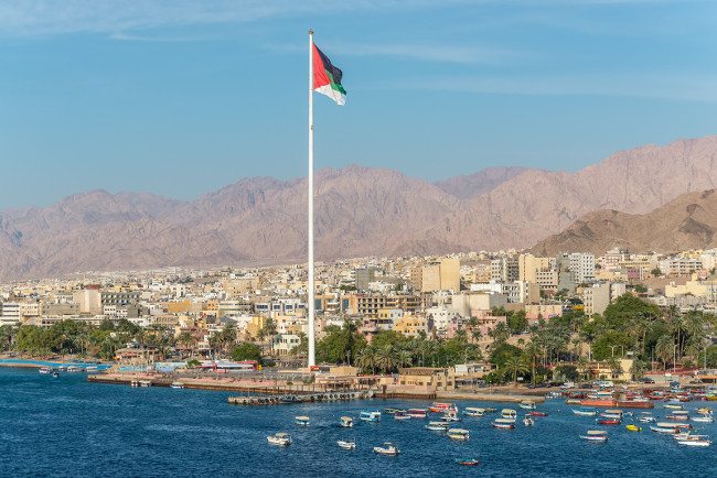 Aqaba, Jordan - November 6, 2017: Cityscape of Aqaba and flag of Jordan waving over the city.  Arab Flag of Revolt-Sixth Tallest Flagpole in the World.