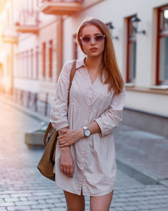 Fashionable young hipster woman in stylish sunglasses in a fashionable white dress with a fashionable brown leather bag walks in the city against the backdrop of orange sun glare. Stylish girl.