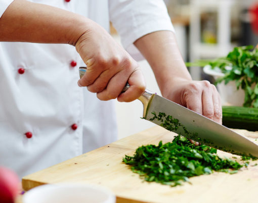 Chef cutting greenery with sharp professional knife on wooden board while cooking in the kitchen