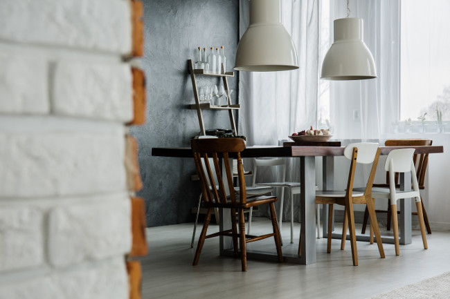 Chic dining room design with concrete wall and industrial chairs