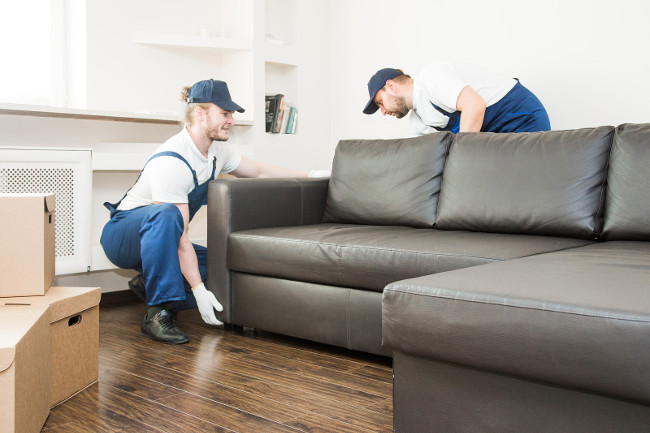 Delivery man move furniture carry sofa for moving to an apartment. professional worker of transportation, male loaders in overalls