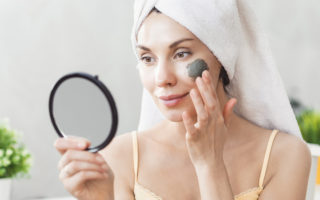 Face Skin care. Attractive Young Woman Wrapped in Bath Towel, applying clay mud mask to face. Skin care concept. Girl taking care of complexion. Beauty treatments