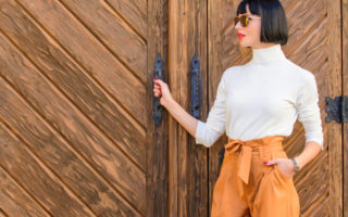 Fashionable outfit slim tall lady. Fashion and style concept. Woman walk in elegant outfit. Woman fashionable brunette stand outdoors wooden background. Girl with makeup posing in fashionable clothes