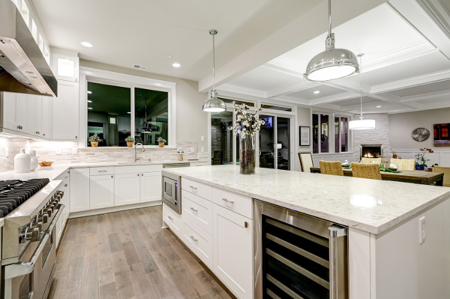 Gourmet kitchen features white shaker cabinets with marble countertops stone subway tile backsplash and gorgeous kitchen island. Northwest USA
