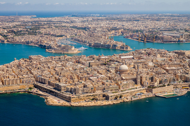 Malta aerial view. Valetta, capital city of Malta, Grand Harbour, Senglea and Il-Birgu or Vittoriosa towns, Fort Ricasoli and Fort Saint Elmo from above. Marsaxlokk city and Freeport in background.