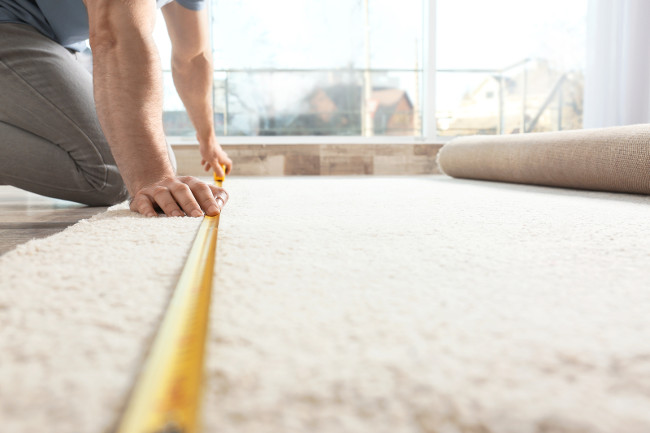 Man measuring carpet indoors. Construction tool closeup