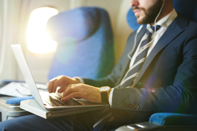 Mid section portrait of unrecognizable businessman typing on keyboard while using laptop during first class flight in plane, copy space