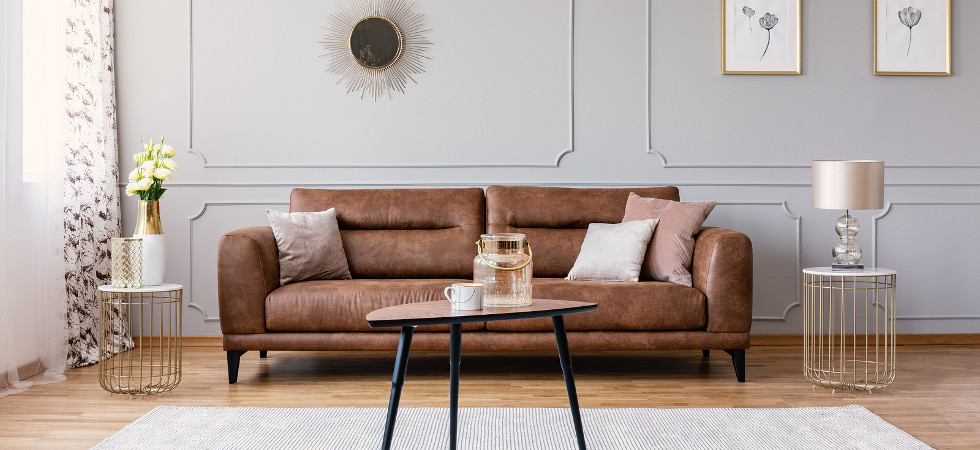 Minimal interior design of living room with brown leather couch, retro armchair coffee table and golden decorations, real photo