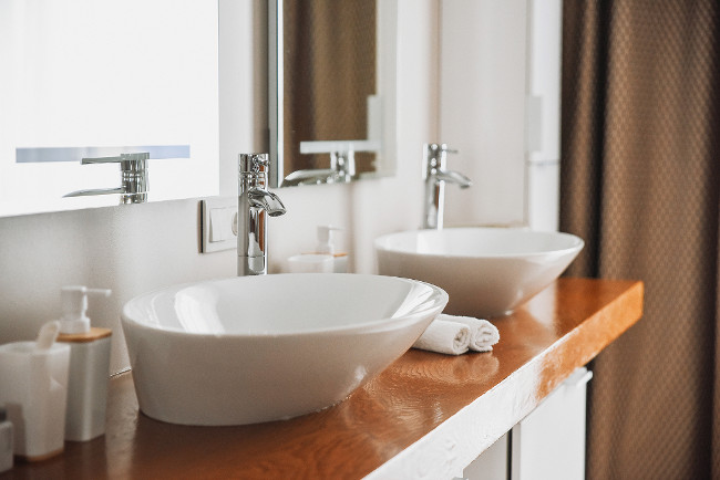 Modern stylish washbasins with chrome taps. Contemporary interior. Luxury lifestyle. Wood texture
