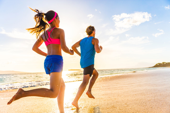 Runners fitness couple running training on beach. Morning cardio workout people doing exercise.Active sports lifestyle.