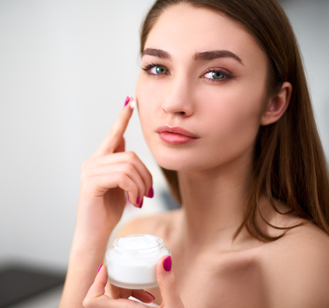 Smiling young mixed race woman applying face cream on her perfect skin. Model with flawless skin holding white jar of cream on blurred grey background in cosmetology clinic.