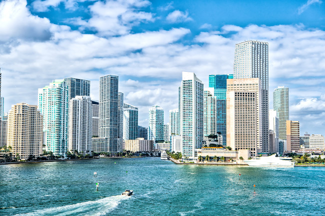 miami skyline. luxury Yachts sail on sea or ocean water to city skyscrapers on cloudy blue sky in Miami, USA. Summer vacation, wanderlust, travelling, lifestyle concept.