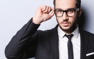 Portrait of handsome young man in formalwear adjusting his glasses while standing against grey background