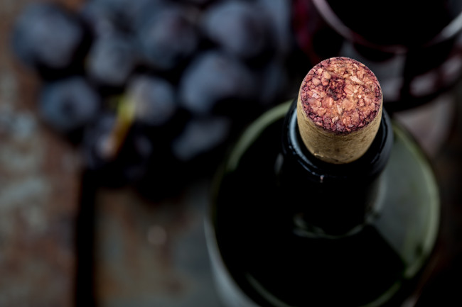 Top view of red wine bottle. Macro, selective focus on wine cork. Wine bottle, glass and grape on vintage background. Copi space, wine concept.