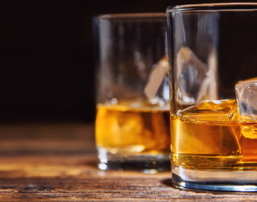 Two glasses of whiskey with ice cubes served on wooden planks. Vintage countertop with highlight and a glass of hard liquor