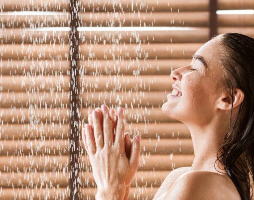 Woman Taking Shower Enjoying Water Splashing On Her, Side View