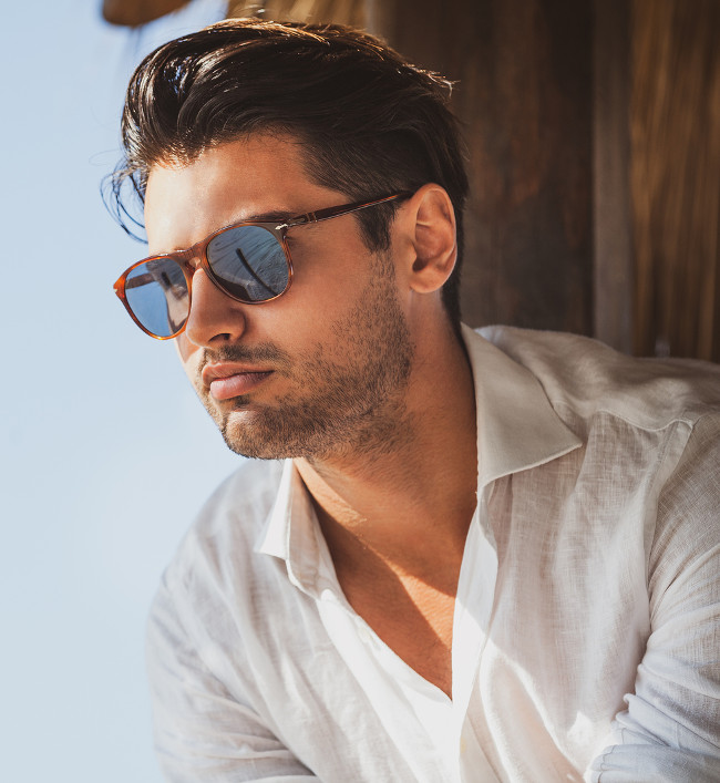Young and handsome man with sunglasses looking. Warm summer lights, he wears a white shirt. Light short beard. Fashionable hair.