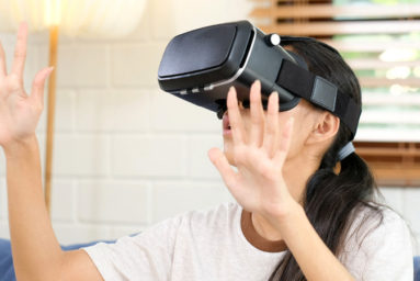 Young asian woman exciting in VR headset looking up and trying to touch objects in virtual reality at home living room, Teenager girl playing VR headset, people and leisure virtual reality technology