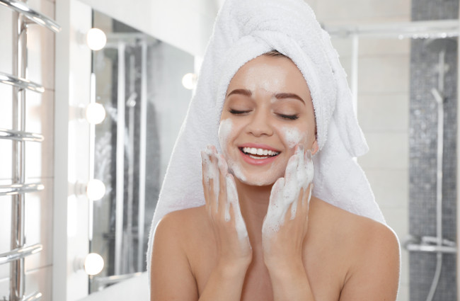 Young woman washing face with soap in bathroom