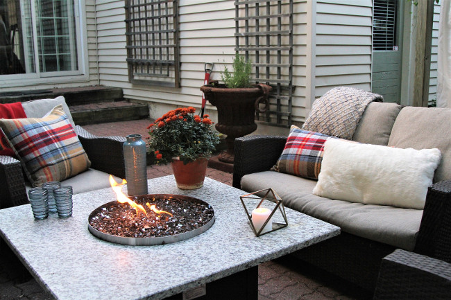 Outdoor seating arrangement  with wicker, pillows, and a table with gas heater