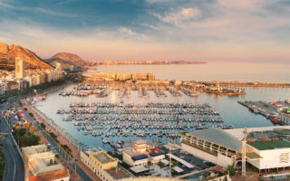 Aerial photography drone view Alicante cityscape above panorama main landmark in city center Santa Barbara castle on the Mount Benacantil moored yachts in the harbour Mediterranean sea at sundown, busy road along seaside, copy space. Spain