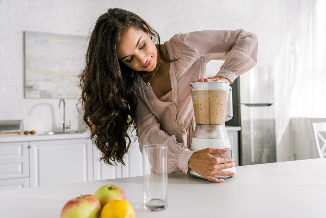 attractive pregnant woman preparing tasty smoothie in blender