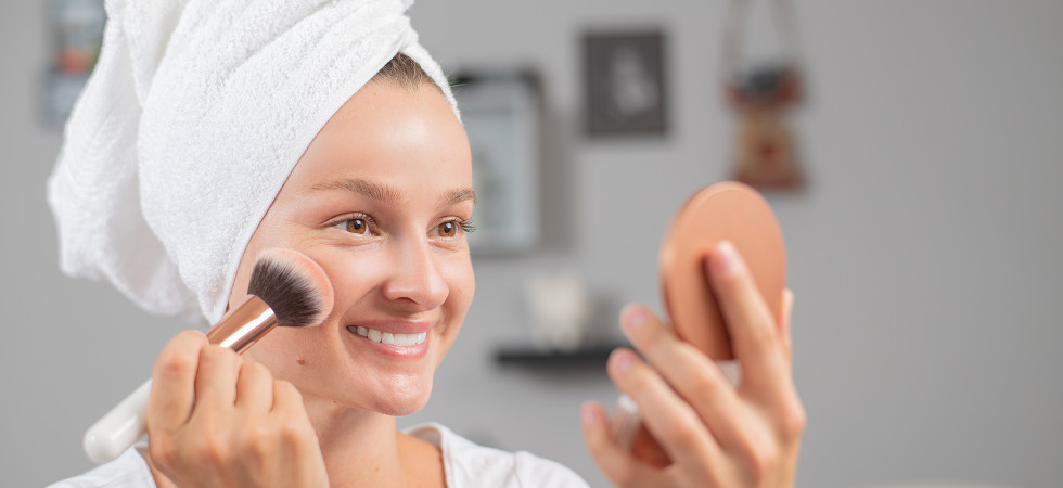 Beautiful woman applying makeup. Pretty girl applying rouge with a brush.