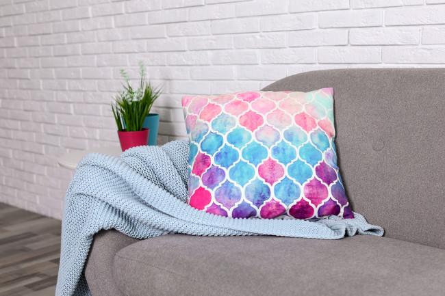 Cozy sofa with pillow and plaid near brick wall. Idea for living room interior design