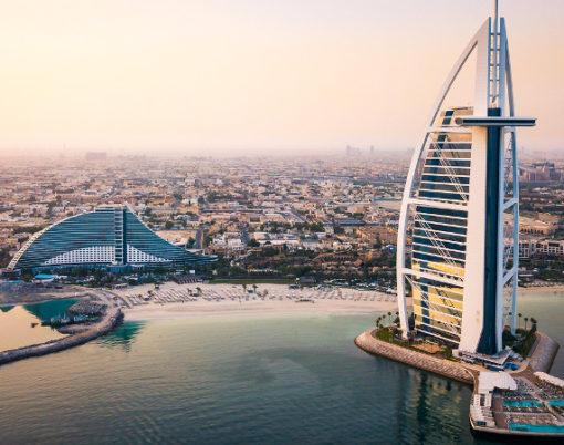 Dubai, United Arab Emirates - June 5, 2019: Dubai seaside skyline and Burj Al Arab luxury hotel aerial view at sunrise